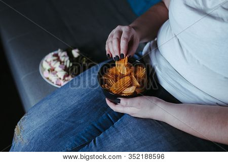 Nerve Food, Addiction, Eating Disorders, Bulimia. Overweight Woman Sit On The Coach Overeating Junk
