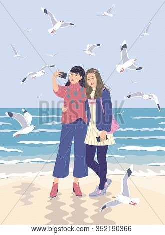 Young Women Taking Selfie Photo On Smartphone At The Sea Coast. Girlfriends With Mobile Phone On Ser