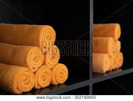 Lots Of Orange Rolled Towels On A Shelves