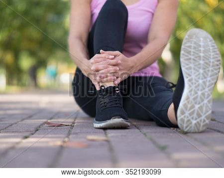 Headless Body Of Caucasian Woman In Sports Wear Who Sitting On The Paved Path In Public Park In Summ