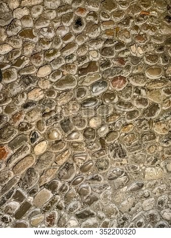 Ground Of River Pebble Stones. Old, Weathered And Scuffed Cobblestones, Made Of Round River Stones O