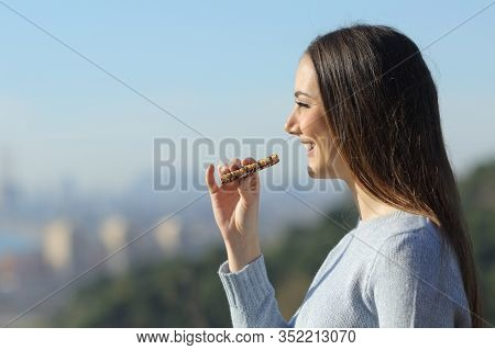 Happy Girl Eating A Snack Bar In The City Outskirts While Contemplating The Views