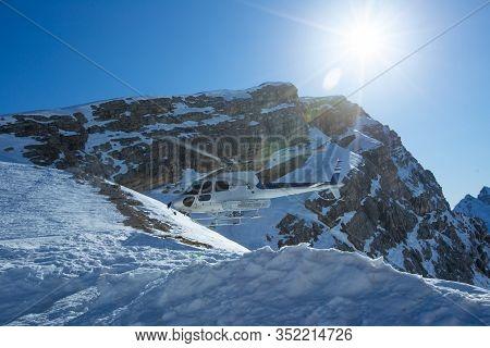Heli Skiing Helicopter Is Landingin Mountains