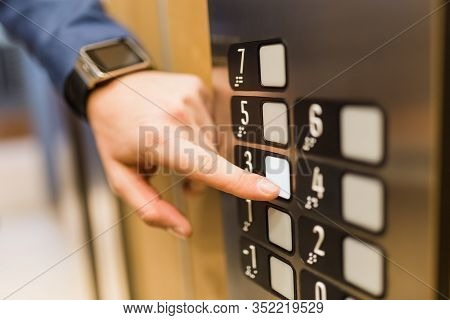 Close Up Of Businessman Pressing Third Floor Control Panel Button In Elevator.