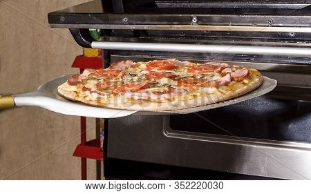 Cooking Pizza In A Pizzeria. Pizza Is Placed On A Spatula In A Baking Oven. For The Menu And Adverti
