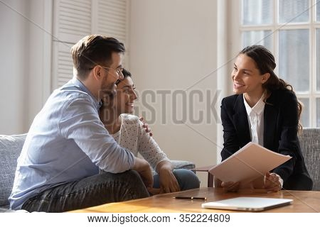 Client And Banker Seated On Sofa Discuss Mortgage Contract Terms