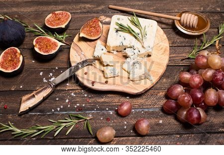 Roquefort  Or Blue Cheese Serving With Grapes, Honey And Figs. Cheese Plate.