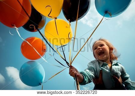 Happy birthday boy with colorful balloons over blue sky background, sincere emotions of a pretty child enjoying life
