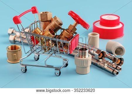 Red Shopping Cart With Plumbing Fittings Closeup. Brass Valve, Filter, Tee In Basket. Sealing Tape,