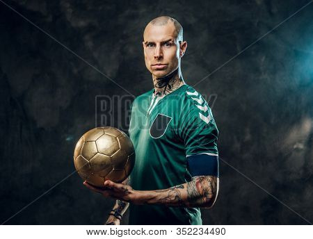 Bold And Handsome Soccer Player Posing For A Photoshot In A Dark Studio, Wearing Green Professional