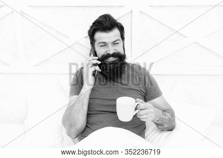 Good Morning. Hello Dear. Bearded Man Using Mobile Technology In Bed. Handsome Guy Talking On Phone