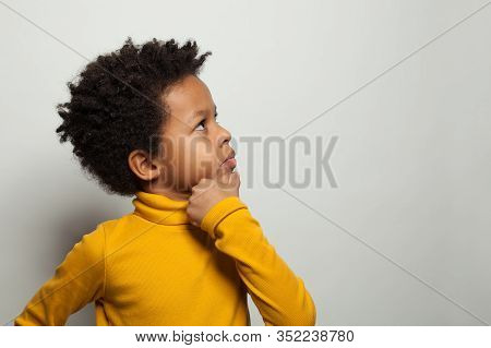 Small Black Kid Boy Thinking And Looking Up On White Background