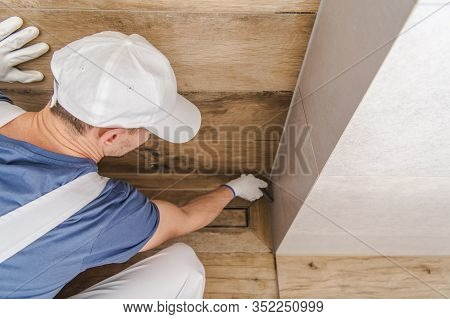 Contractor Worker Sealing Bathroom Shower Cabin Ceramic Tiles. Interior Remodeling.