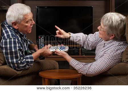 Senior Couple Arguing Over Tv Remote Control