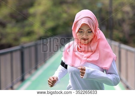 Portrait Young And Beautiful Asian Muslim Woman In Sportswear Jogging Outdoor For Marathon Training.