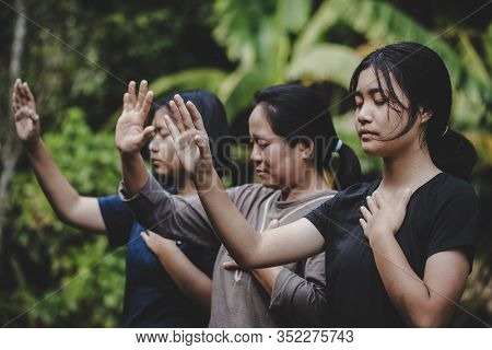 Group Of Different Women Praying Together
