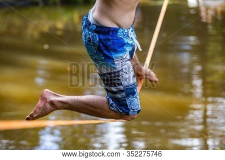 A Young Man Risks Getting Wet In A Lake As He Performs Slack Wire Stunts, Wearing Colorful Swimming