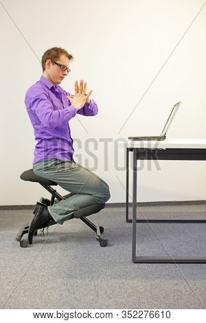 male office worker sitting on kneeling stool, exercising during short break in work at his desk in the office