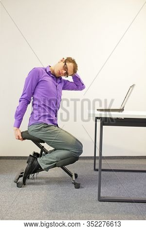 male office worker sitting on kneeling stool, stretching neck during short break in work at his desk in the office