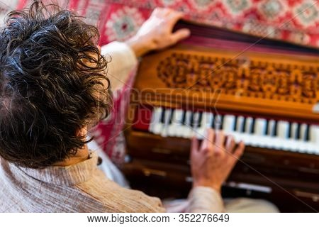 High Angle View Of Young Male Shamanic Playing Kirtan Music Using Musical Instrument Harmonium For M