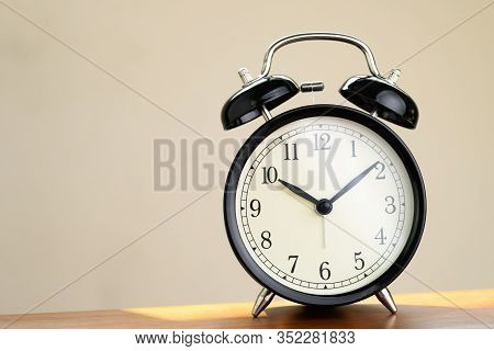 Black Retro Alarm Clock At Ten O'clock In The Afternoon On Wooden Table With Sun Light., Schedule At