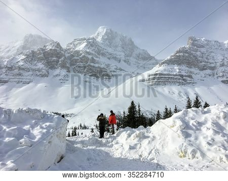 A Family Admiring An Incredible View Of A Dark Green Forest In The Foreground And Snow Covered Mount