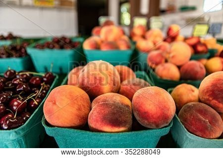 Close Up Neatly Arranged Rows Of Green Cardboard Boxes Filled With Peaches. Fresh Plump Fruit On Sal