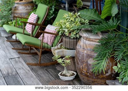Colorful Green Rocking Chairs In A Cottage Garden Porch Setting On Wooden Floor In Vintage Thai Bota