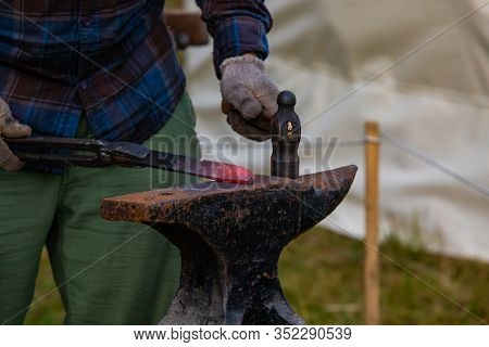 Closeup View On The Hands Of A Traditional Artisan At Work. Metalworker Uses Blacksmith Anvil And Da