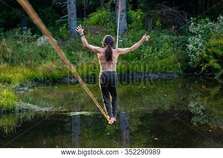 A Male Slack Wire Artist Is Seen Practicing Slacklining Over A Water Pond In Nature, Balancing On Ro