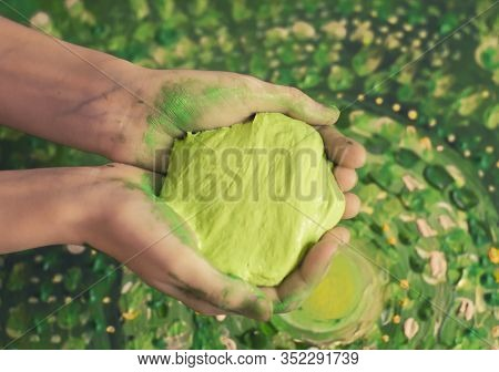 Light Green Slice In Hands On A Picturesque Background. Toy For Children Photo.