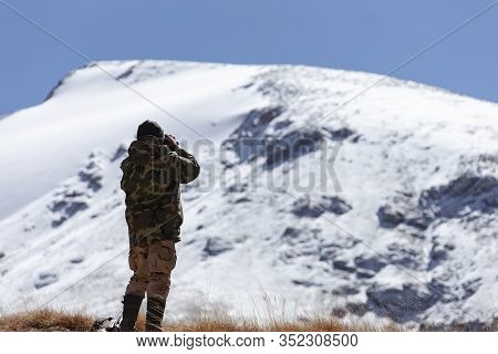 Hunter In The Mountains In Camouflage Looks Through Binoculars. A Man In A Hunting Camouflage Jacket