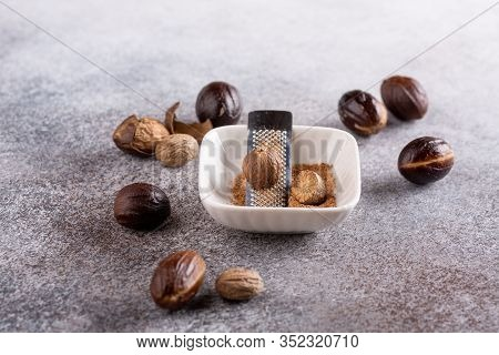 Nutmeg Seed And Ground Nutmeg With Grater On Concrete Background. Freshly Grated Spice In White Bowl