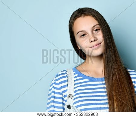 Brunette Adolescent In Jeans Overall And Striped Sweatshirt. She Is Smiling While Posing Against Blu