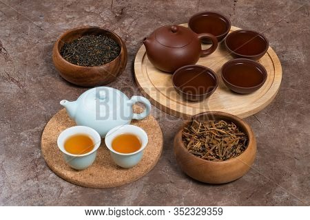 Chinese Tea Ceremony. Porcelain Tea Ware And Clay Tea Ware With Chinese Tea In Wooden Bowls On Stone