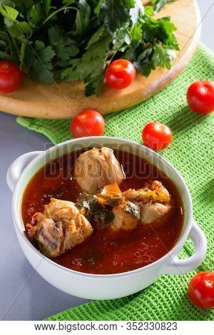 Chakhokhbili With Chicken Legs, Parsley And Tomatoes On A Gray Background. Chicken In Tomato Sauce.