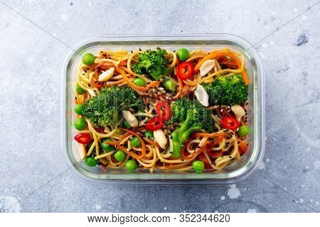 Stir Fry Noodles, Udon With Vegetables In Glass Lunch Box. Grey Stone Background. Top View.