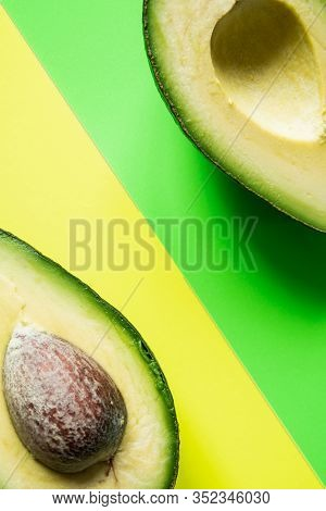 Ready To Eat Avocado Cut Into Two Halves, Isolated On Green And Yellow Background