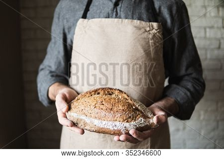 Man In Rustic Apron Holding A Loaf Of Bread In His Hands