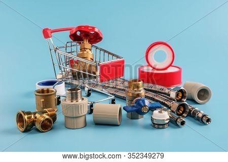 Red Shopping Cart With Brass Gate Valve Closeup. Ball Valve, Coupling, Corner, Sealing Tape, Flexibl
