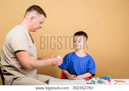 First Aid. Medicine Concept. Kid Little Doctor Sit Table Medical Tools. Health Care. Medical Examina