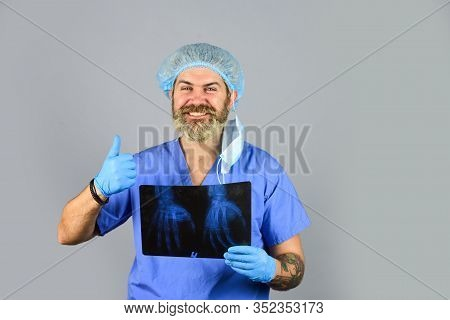 Hospital Emergency. Doctor Compares Results. X Ray Radiation. Doctor Holds Pictures Of Bones. Fractu