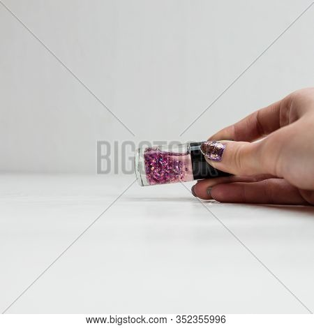 Hand Holding Glittery Colorful And Bright Nail Polish Isolated With Copy Space.