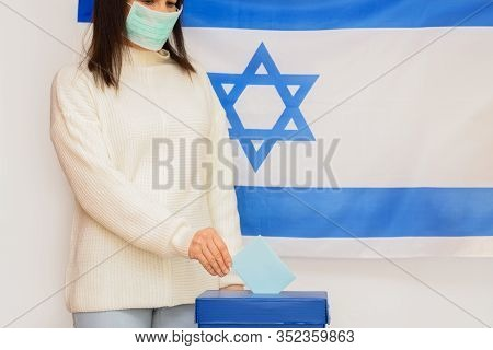 Elections Israel. Woman With Face Mask Put Ballot Paper In A Box For Ballot In Election On Israel Fl