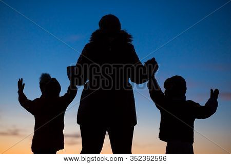 Strong Woman Brings Up Two Children. Silhouette Of A Woman With Two Happy Children.