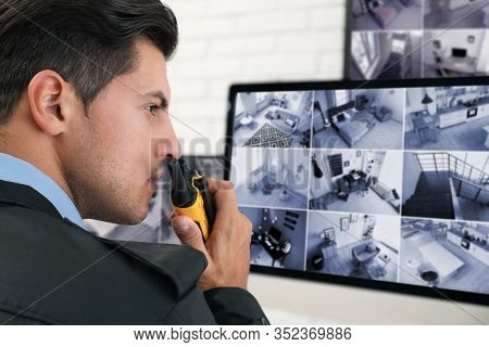 Male Security Guard With Portable Transmitter Near Monitors At Workplace, Closeup