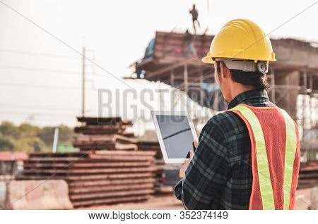 Construction Engineers Are Using Tablets To Inspect Construction Projects On The Background Of The C
