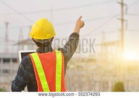 Electrical Engineer Holding And Using A Digital Tablet, Engineer Pointing At High Voltage Substation