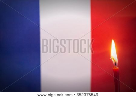 Burning Candle On The Background Of The Flag Of France. The Concept Of Mourning And Sorrow In The Co