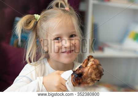 Cute Adorable Caucasian Blond Little Girl Portrait Enjoy Eating Roasted Turkey Shank At Dinner At Re